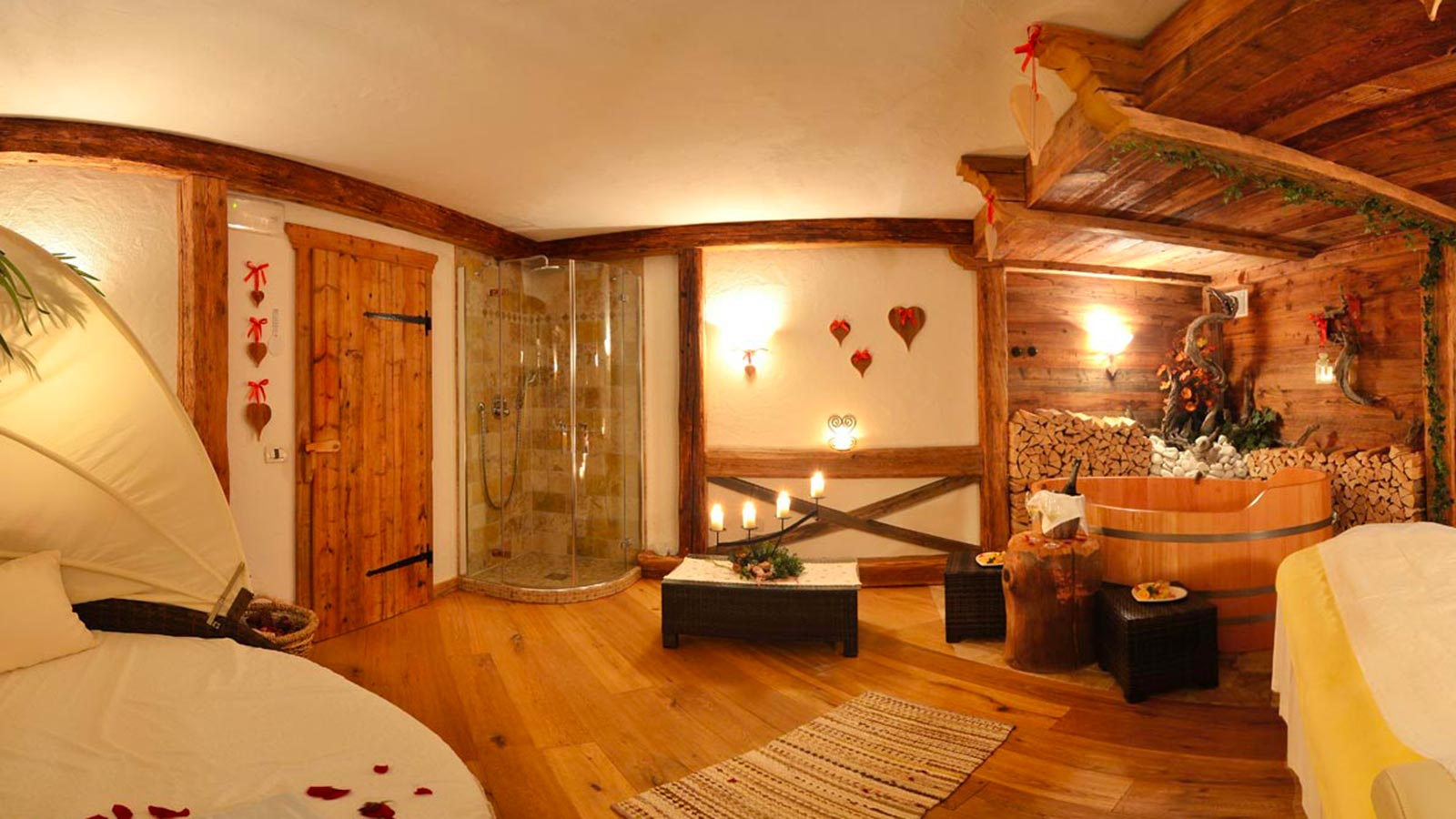cosy relax area of the Hotel Arkadia, on the left a bed strewn with red petals, on the right a cosy wooden bathtub, in the middle a shower
